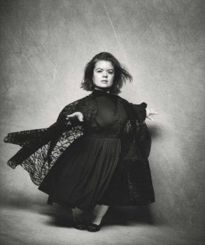 Sinéad Burke photographiée par Peter Lindbergh pose pour Vogue dans une magnifique robe noir. Elle est très élégante.