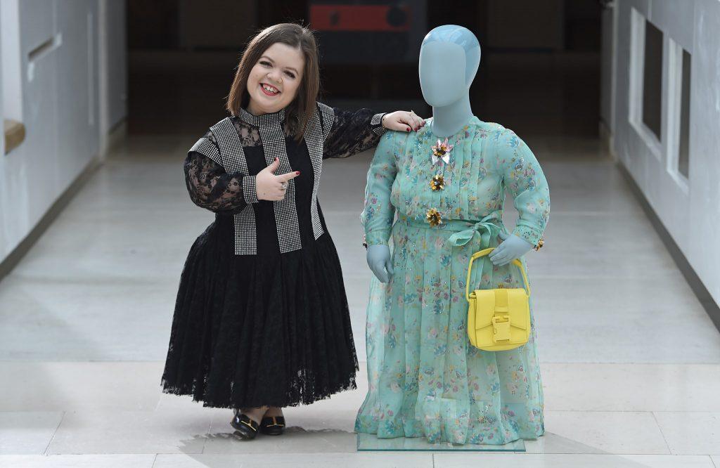 """L'activiste Sinéad Burke pose à côté du premier mannequin """"little person"""" réalisé en 2018 partir de ses dimensions. Le mannequin porte une rob et un sac à main de Christopher Kane, adaptés à partir des modèles de la collection Printemps-Eté 2018."""
